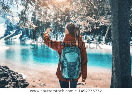 Beautiful young woman with backpack is making selfie on the lake Stock photo © denbelitsky