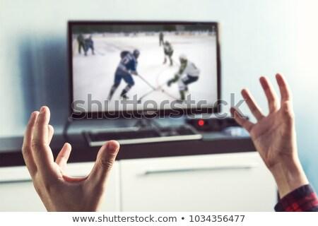 man watching ice hockey game on tv at home stock photo © dolgachov