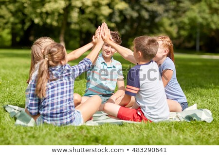 happy friends making high five in park stock photo © dolgachov