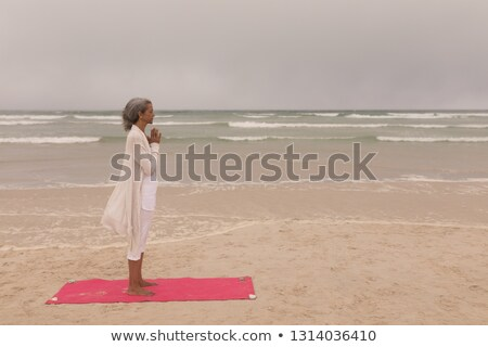 side view of senior woman with eyes closed and hands clasped doing yoga on the beach stock photo © wavebreak_media