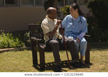 Front view of young smiling female doctor talking with happy senior man hands leaning on a cane whil Stock photo © wavebreak_media