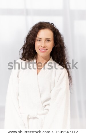 Healthy young charming woman with toothy smile wearing white soft bathrobe Stock photo © pressmaster