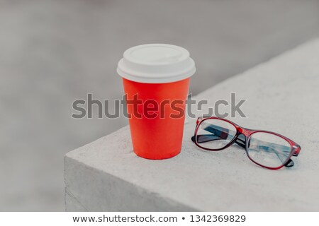 Red disposable cup of hot beverage on white concrete wall, optical glasses near. Takeaway coffee in  Stock photo © vkstudio