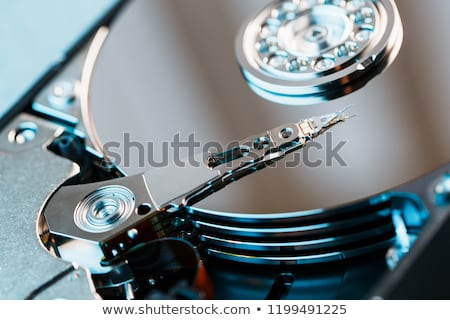 Stock photo: parts of hard disk drive with information on magnetic surface