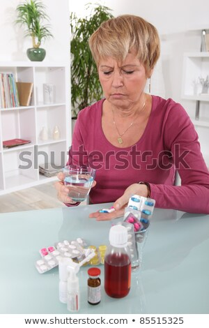 Grumpy woman taking her pills Stock photo © photography33