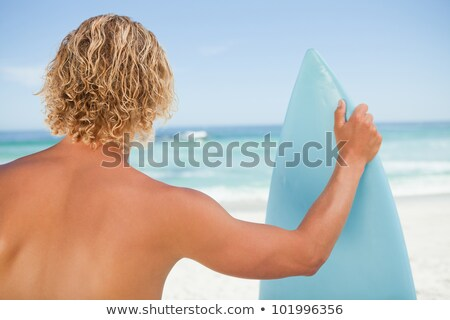A young blonde man holding a perched surfboard Stock photo © wavebreak_media