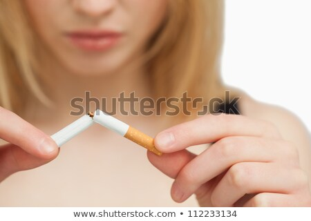 Stock photo: Fingers breaking a cigarette against a white background