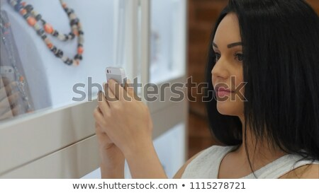 Young woman looking at the shop showcase and taking earrings Stock photo © HASLOO