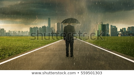 businessman with black umbrella protecting from rain stock photo © stevanovicigor