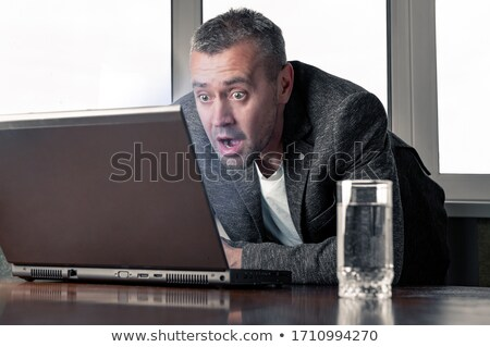 Caucasian businessman working on laptop with wide eyed expressio stock photo © dgilder