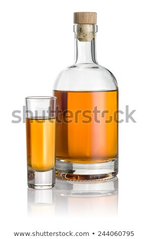 Bottle and high shot glass filled with amber liquid Stock photo © Zerbor