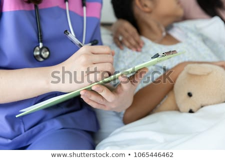 Doctor writing patient test results Stock photo © HASLOO