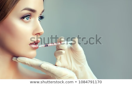 doctor gets botox injection to a woman patient Stock photo © Flareimage