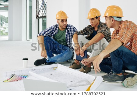 Team of architects sitting on floor with construction plans  Stock photo © Kzenon
