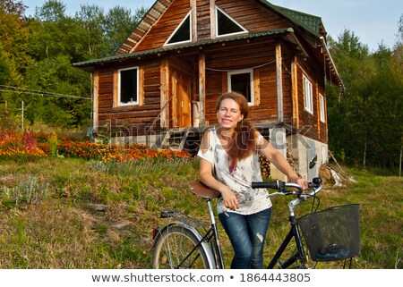 beautiful woman with flower near old wooden house Stock photo © Aikon