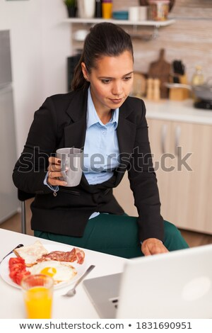 Satisfied businesswoman drinking coffee to go and looking mobile Stock photo © stevanovicigor