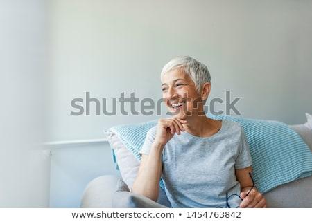 Nő ül kanapé otthon másfelé néz portré Stock fotó © deandrobot
