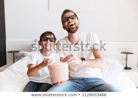 joyful boy on sofa watching tv with 3d glasses stock photo © deandrobot