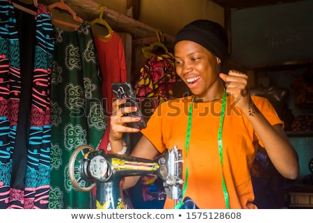 Woman in tailor's shop with phone Stock photo © dash
