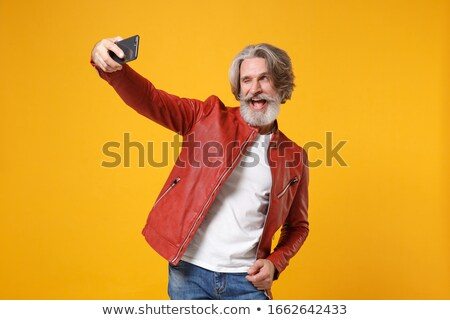 guy in leather jacket taking picture with mobile phone stock photo © deandrobot