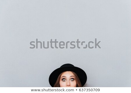 Woman in hat peeping out from the edge Stock photo © deandrobot
