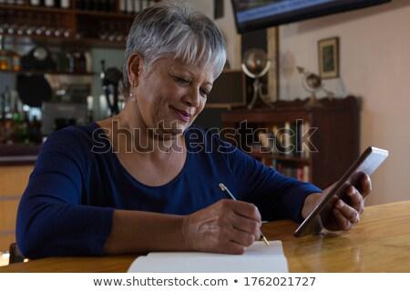 Waitress using her mobilephone Stock photo © wavebreak_media