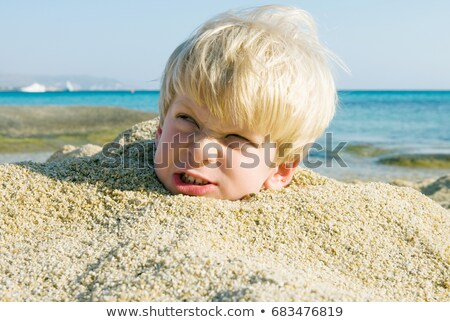 Young boy buried in the sand scowling Stock photo © IS2