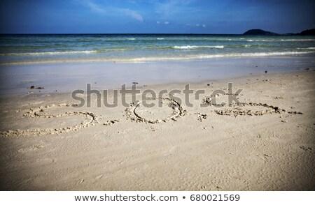 Sos escrito areia praia água Foto stock © Gertje