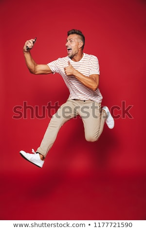 Full length photo of caucasian man in striped t-shirt jumping an Stock photo © deandrobot