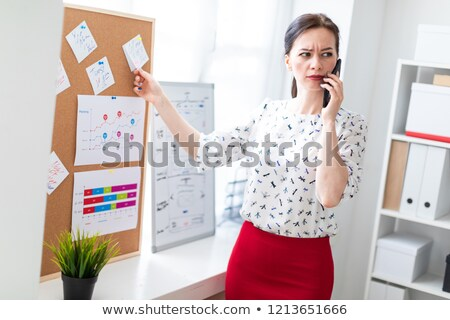 A young girl is standing near the board with stickers and talking on the phone. Stock photo © Traimak