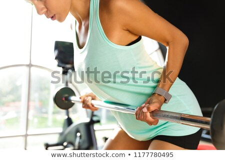 Cropped image of Calm sports woman doing exercise with barbell Stock photo © deandrobot