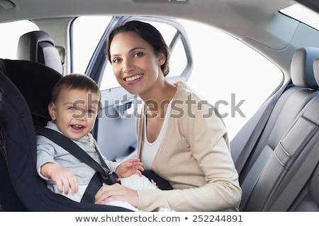 Mother securing her boy in the car seat in   Stock photo © Lopolo