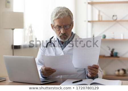 doctor reading the medical history of a senior man Stock photo © nito