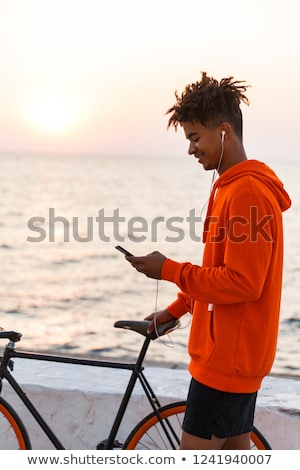 young african guy outdoors on the beach using mobile phone listening music walking with bicycle stock photo © deandrobot