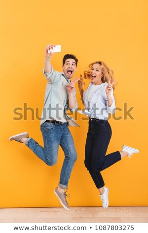 Full length photo of excited couple man and woman jumping while  Stock photo © deandrobot