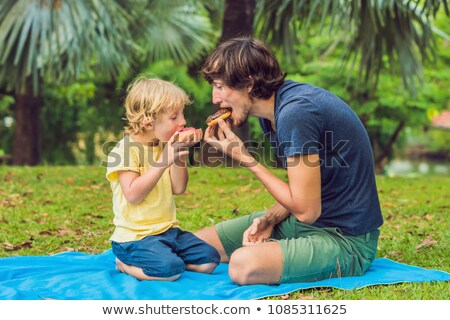 Dad and son are eating a donut in the park. Harmful nutrition in the family Stock photo © galitskaya