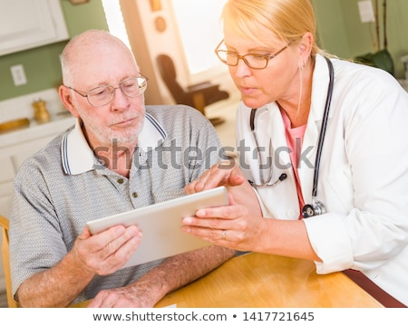 Female Doctor or Nurse Showing Senior Man Touch Pad Computer At  Stock photo © feverpitch