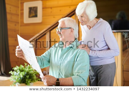 Happy mature man and his wife reading latest news Stock photo © pressmaster