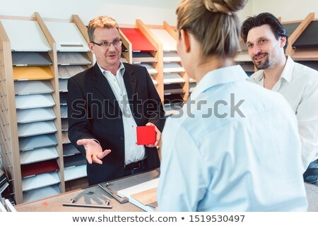 salesman explaining options for colors and materials of new kitchen stock photo © kzenon