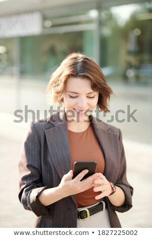 Jovem empresária mensagens bem sucedido olhando Foto stock © pressmaster