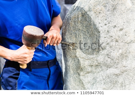 Stonemason working on boulder with sledgehammer and iron Stock photo © Kzenon