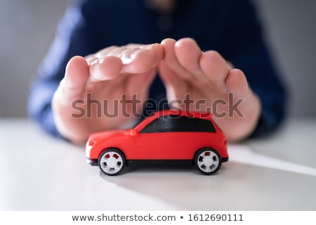 Businessman's Hand Protecting Red Toy Car Stock photo © AndreyPopov