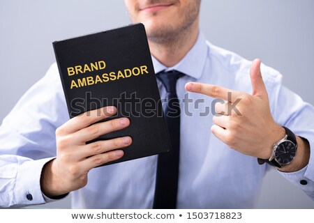 ストックフォト: Man Holding Book With Brand Ambassador Text
