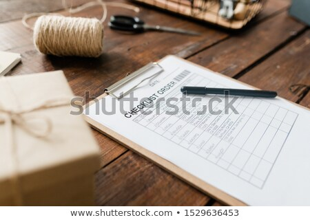 Clipboard with document and pen, spool of threads, packed box and other items Stock photo © pressmaster