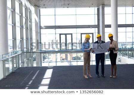 Front view of multi-ethnic architects discussing over blueprint in modern office Stock photo © wavebreak_media