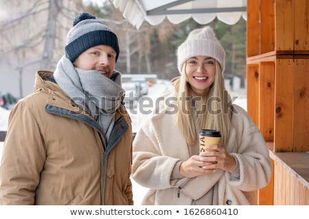 Happy young heterosexual couple in casual winterwear standing by stall Stock photo © pressmaster