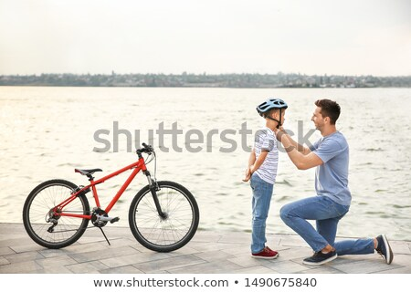 father help his child to put his helmet Stock photo © Lopolo
