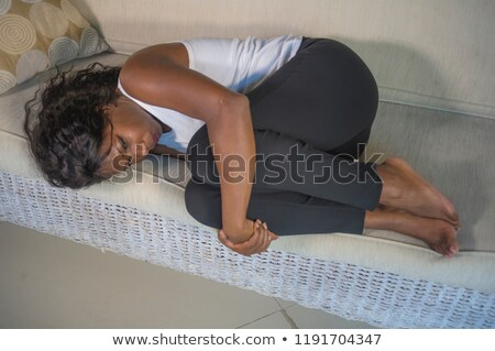 Young Black Woman With Menstrual Pain Lying On Sofa Stock photo © diego_cervo