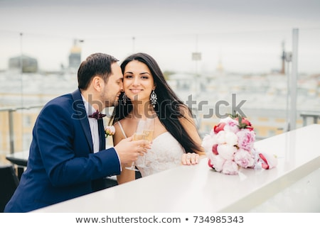 Romantic newlyweds drink champagne, clink glasses, being very happy to celebrate their wedding, feel Stock photo © vkstudio
