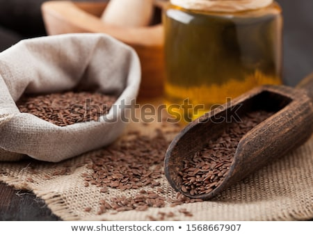 Glass jar of raw natural organic linseed flax-seed with spoon on wooden background. Healthy omega 3  Stock photo © DenisMArt